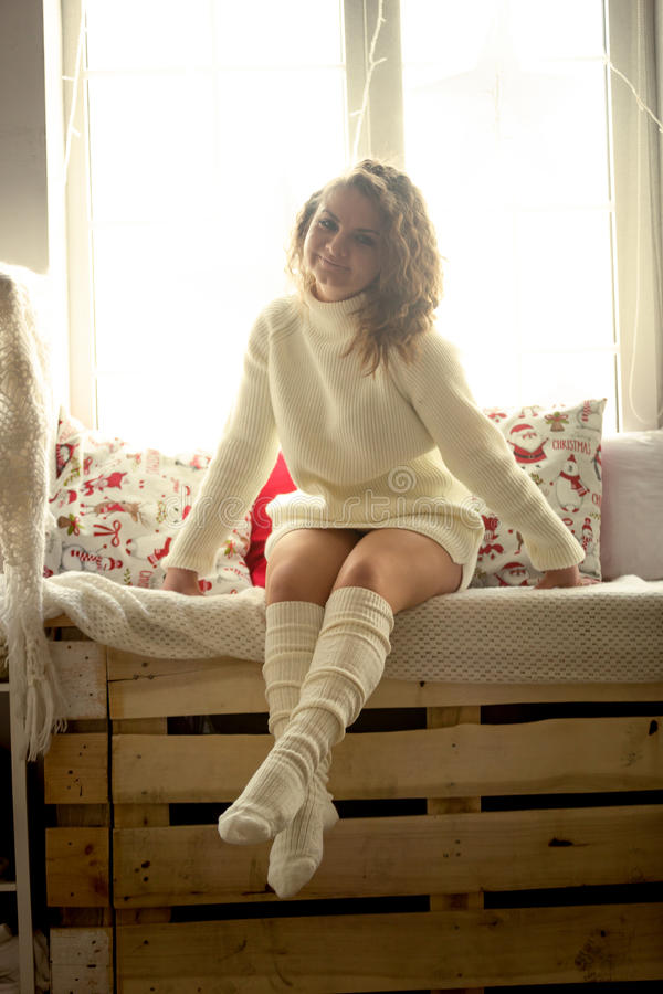 Foto tonificada da mulher bonito na camiseta e das peúgas que sentam-se na janela imagens de stock