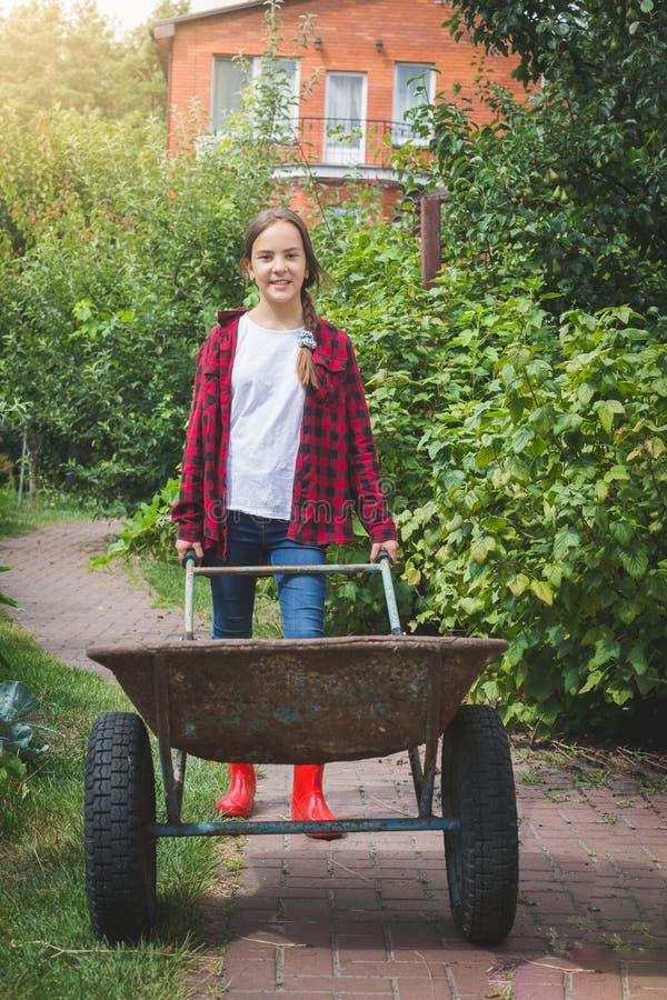 Foto tonificada do adolescente de sorriso que puxa o whellbarrow velho grande no jardim fotos de stock