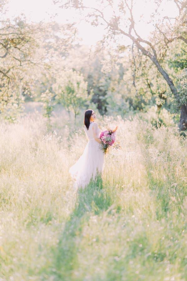 Foto traseira da noiva que olha de trás e que guarda o ramalhete grande das flores no meio do campo foto de stock royalty free