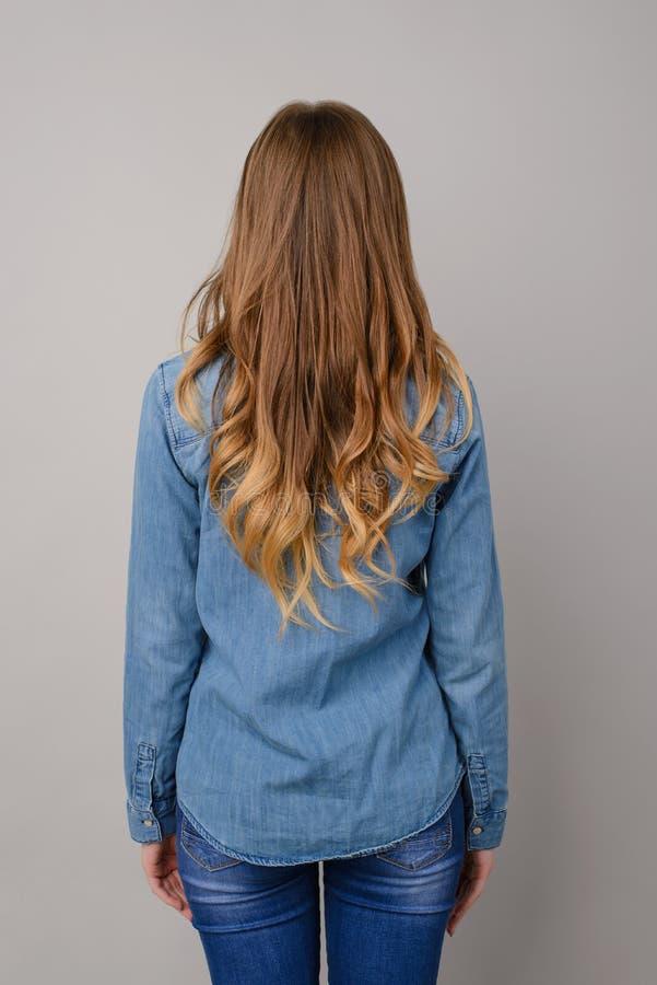A foto traseira da vista da jovem mulher vestiu-se na roupa das calças de brim, ela tem imagens de stock royalty free