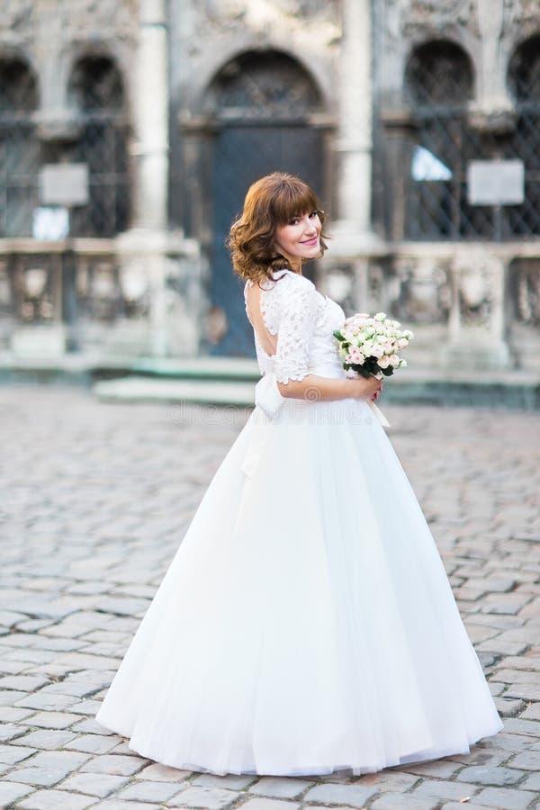 Foto trasera integral de la novia en el vestido de boda largo que sostiene el ramo Ubicación de la calle imágenes de archivo libres de regalías