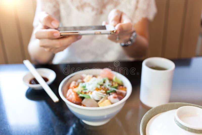 Foto vaga della giovane donna che fotografa alimento giapponese fotografia stock libera da diritti