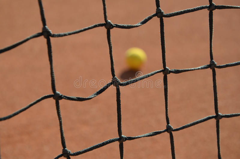 Foto vaga pallina da tennis attraverso la rete di tennis immagine stock