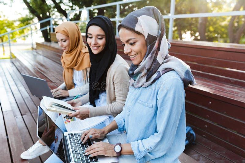 Foto van aantrekkelijke Islamitische vrouwen die headscarfs het rusten in groen park dragen stock foto's