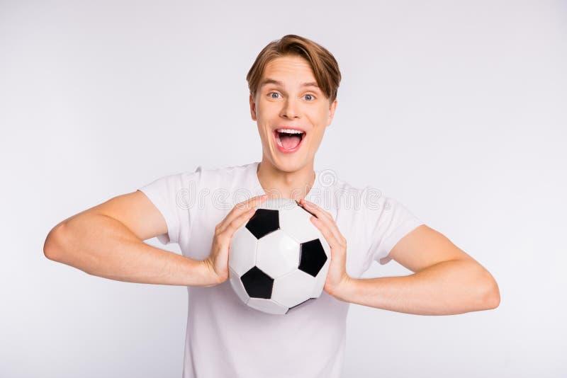 Foto van aantrekkelijke kerel die grote het spelen bal houden die favoriete toevallige de uitrustings witte achtergrond toejuiche stock afbeelding