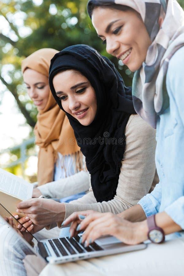 Foto van aantrekkelijke moslimmeisjes die headscarfs het rusten in groen park dragen stock foto's