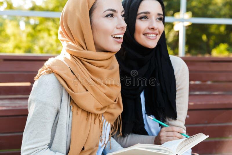 Foto van aantrekkelijke moslimmeisjes die headscarfs zitting in groen park dragen royalty-vrije stock afbeeldingen