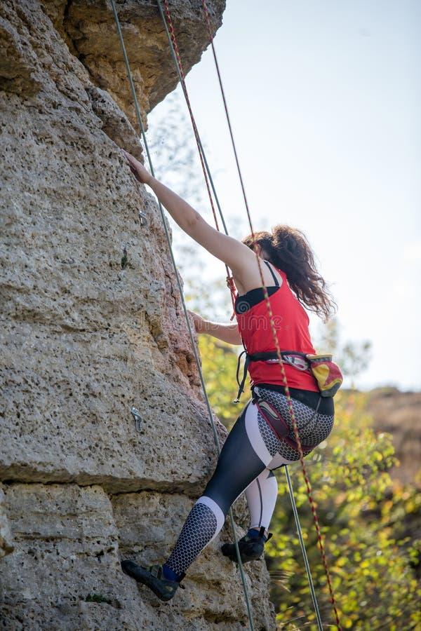 Foto van atletenmeisje het klauteren over rots stock foto's