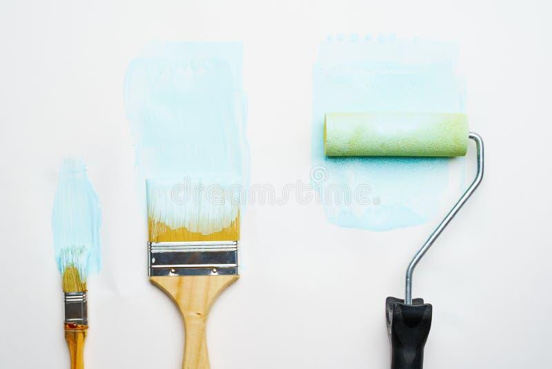 Foto van borstels en rol met blauwe verf stock foto