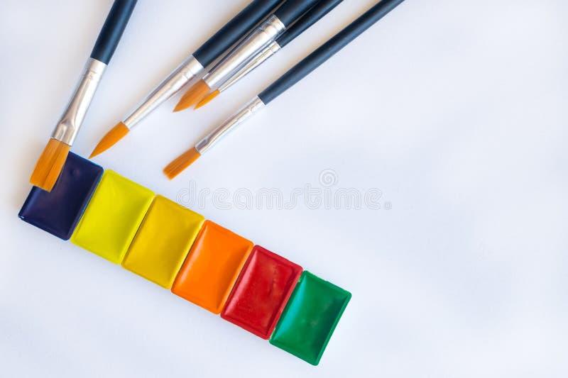 Foto van borstels voor waterkleur het schilderen dicht omhoog en reeks waterverfverven in cuvettes stock afbeeldingen