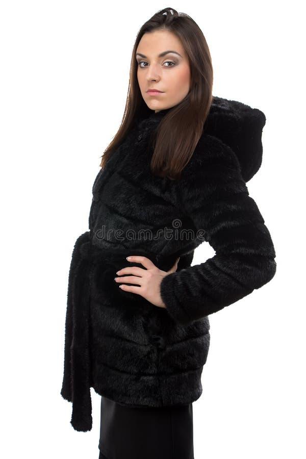 Foto van brunette in valse bontjas met kap stock afbeelding