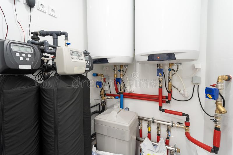 Foto van centrale hydraulische boiler in lichte heldere ruimte met rood pijpen het verwarmen element en slim controlebord royalty-vrije stock afbeeldingen