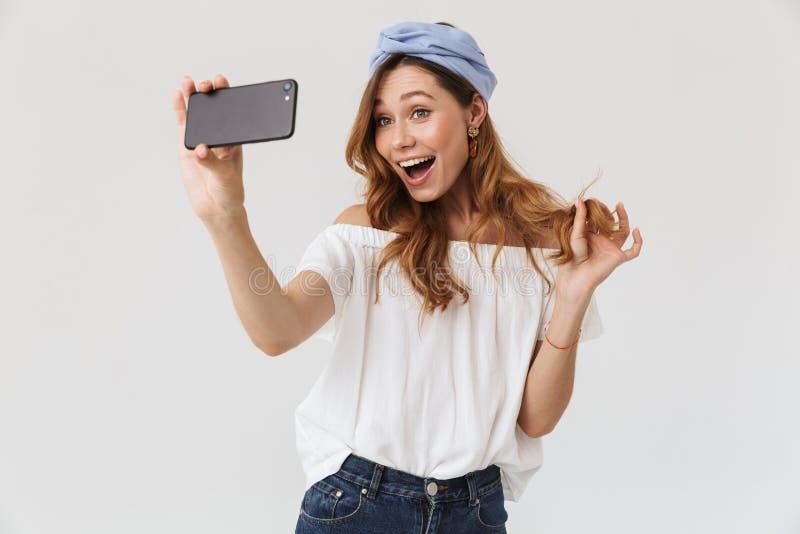 Foto van charmante jonge vrouwenjaren '20 die terwijl het nemen van selfie o lachen stock foto's