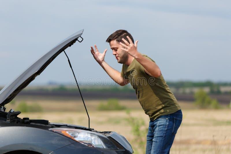 Foto van de gefrustreerde mens naast gebroken auto met open kap stock afbeeldingen