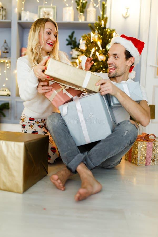 Foto van de gelukkige mens en vrouw in santa GLB met gift in doos stock foto