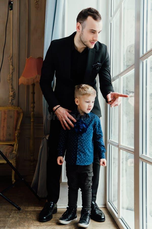 Foto van de gelukkige mens en zijn zoonszitting door het venster stock fotografie