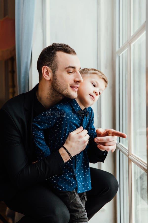 Foto van de gelukkige mens en zijn zoonszitting door het venster royalty-vrije stock afbeelding