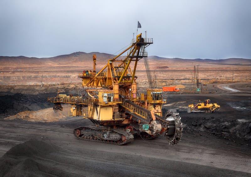 Foto van de kolenmijn Een reusachtig rudimentair graafwerktuig wordt gebruikt voor ladingssteenkool in spoorwagonnen stock foto's