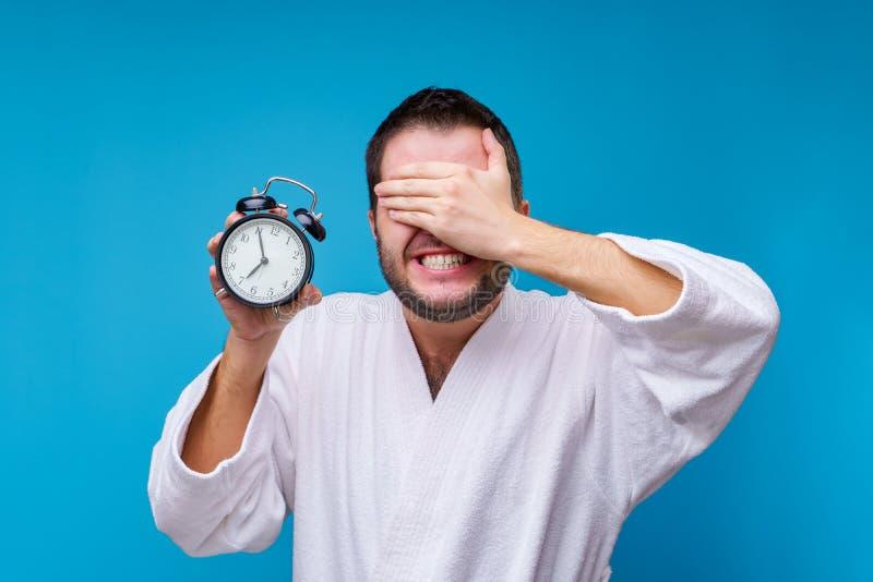 Foto van de mens met een wekker ter beschikking stock fotografie