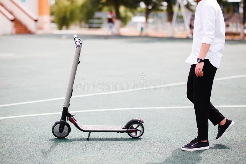 Foto van de moderne mens met elektrische autoped bij de straat royalty-vrije stock afbeelding
