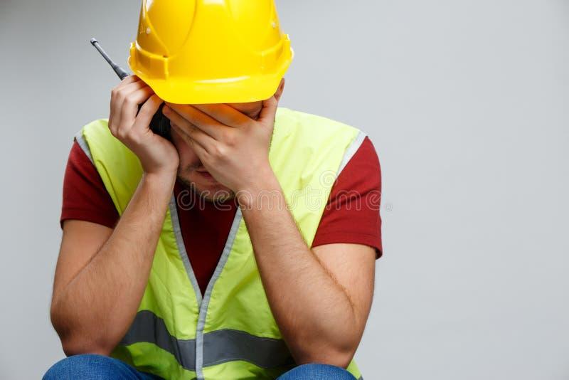 Foto van de ongelukkige bouwersmens in gele helm met walkie-talkie stock fotografie
