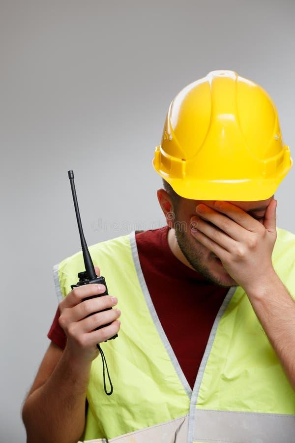Foto van de ongelukkige bouwersmens in gele helm met walkie-talkie op lege grijze achtergrond royalty-vrije stock foto's