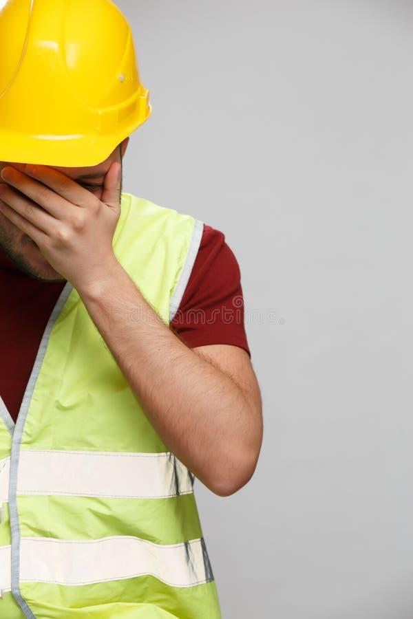 Foto van de ongelukkige bouwersmens in gele helm op lege grijze achtergrond stock foto's