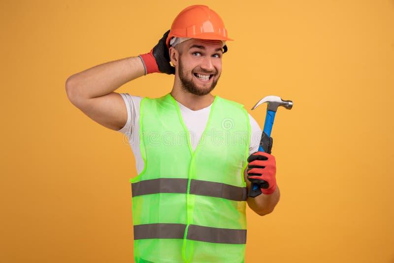 Foto van de ontevreden handyman draait rechts, kijkt in afstand met frontaal gezicht, houdt hamer, is professionele bouwer, beric royalty-vrije stock foto's
