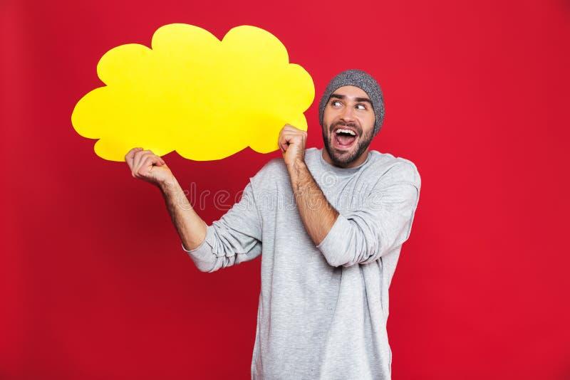 Foto van de positieve mens die en lege gedachte bel glimlachen houden die over rode achtergrond wordt geïsoleerd stock afbeelding