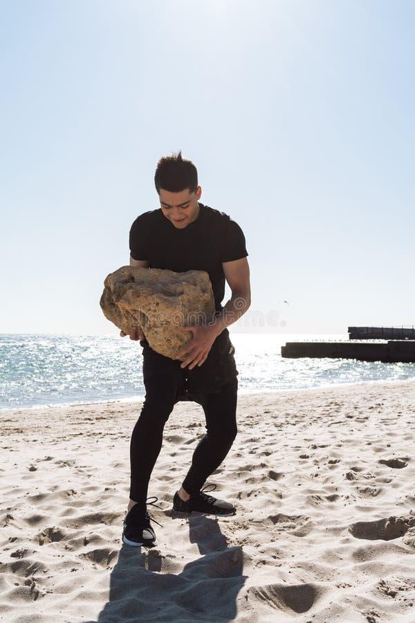 Foto van de sterke donkerbruine mens langs strand door kust lopen en dragende grote steen die in zijn handen royalty-vrije stock afbeelding