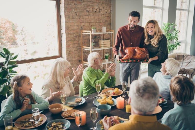 Foto van de volledige familie sit feast gerechten tafel echtpaar echtgenote man met grote geroosterde kalkoengasten klappen wapen stock fotografie