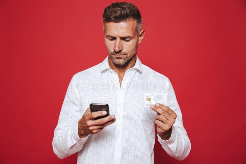 Foto van de volwassen mens in de witte creditcard van de overhemdsholding en smartp royalty-vrije stock foto