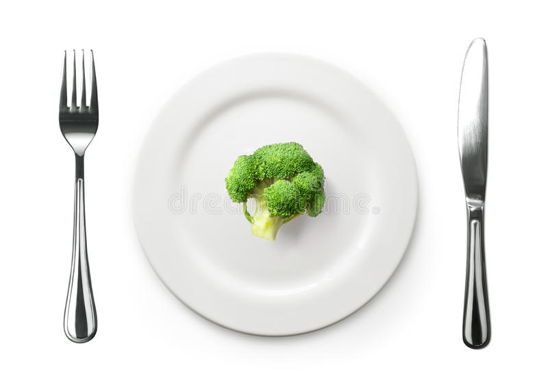 Foto van de vork en het mes met witte plaat en broccoli op whi stock fotografie