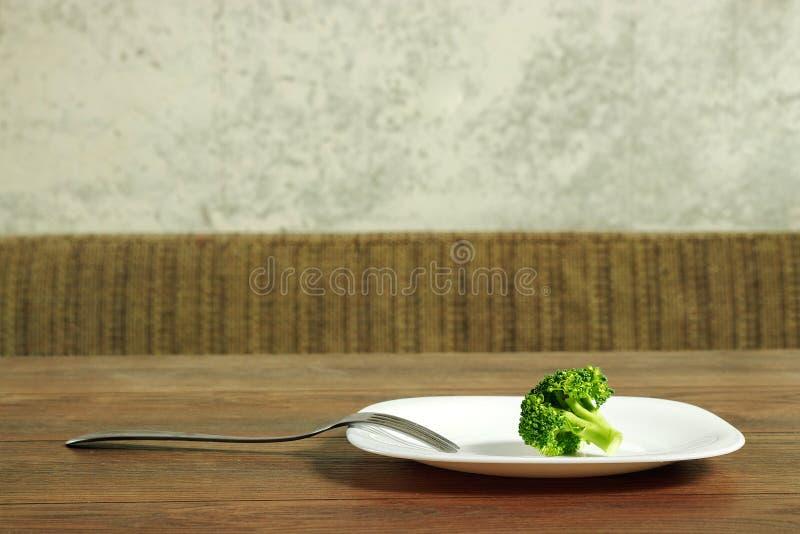 Foto van de vork met witte plaat en broccoli op houttafel Het concept van een gezonde voeding, detox, gewichtsverlies, dieet, ete stock foto