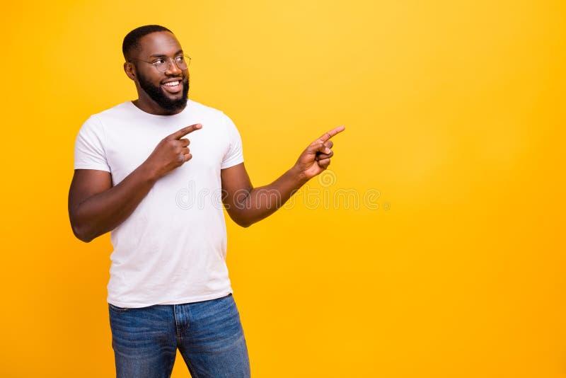 Foto van de vrolijke en genietende van zwarte mens die op niets richten die suspiciously terwijl daar geïsoleerd met levendig sta royalty-vrije stock foto