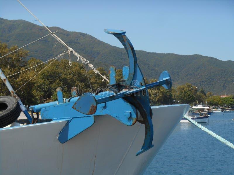 Foto van dichte omhooggaande mening aan roodachtig en blauw anker die zich op voordeel van vissersboot bevinden stock fotografie