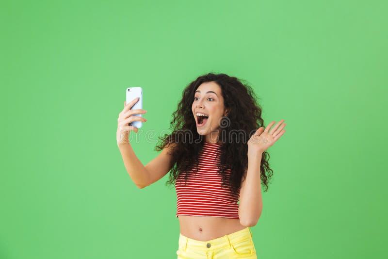 Foto van donkerbruine vrouw die die en celtelefoon glimlachen met behulp van over groene achtergrond wordt geïsoleerd royalty-vrije stock foto