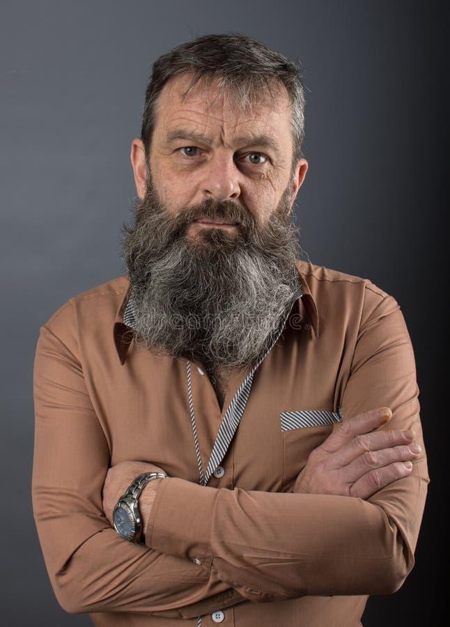 Foto van een boze knorrige oude mens die zeer ontstemd kijken Mannelijke mens met lange baard op zijn gezicht Sluit omhoog gezich stock afbeelding