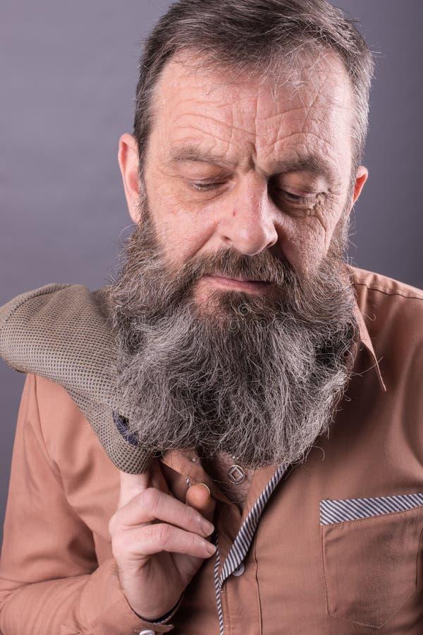Foto van een boze knorrige oude mens die zeer ontstemd kijken Mannelijke mens met lange baard op zijn gezicht Sluit omhoog gezich stock foto