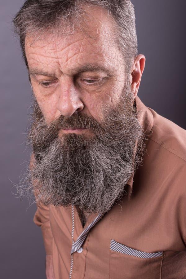 Foto van een boze knorrige oude mens die zeer ontstemd kijken Mannelijke mens met lange baard op zijn gezicht Sluit omhoog gezich royalty-vrije stock afbeeldingen