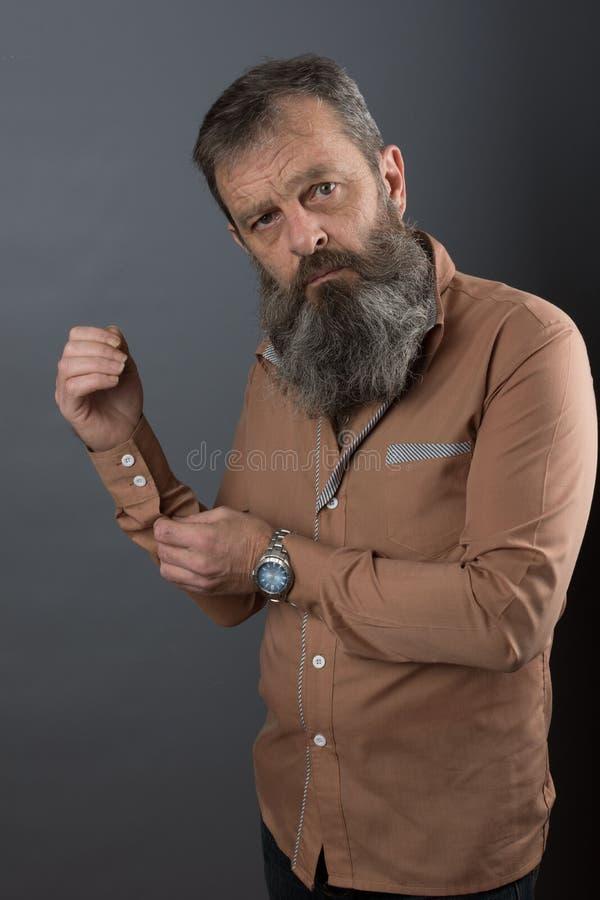 Foto van een boze knorrige oude mens die zeer ontstemd kijken Mannelijke mens met lange baard op zijn gezicht Sluit omhoog gezich stock fotografie