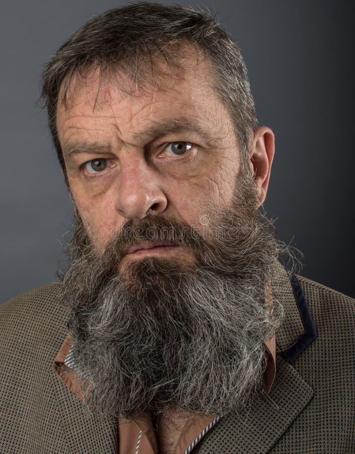 Foto van een boze knorrige oude mens die zeer ontstemd kijken Mannelijke mens met lange baard op zijn gezicht Sluit omhoog gezich stock afbeeldingen