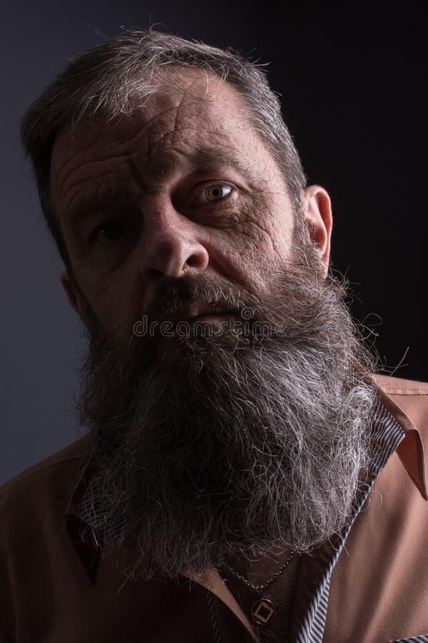 Foto van een boze knorrige oude mens die zeer ontstemd kijken Mannelijke mens met lange baard op zijn gezicht Sluit omhoog gezich royalty-vrije stock foto's