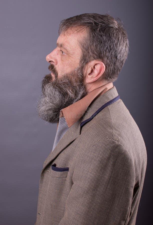 Foto van een boze knorrige oude mens die zeer ontstemd kijken Mannelijke mens met lange baard op zijn gezicht Sluit omhoog gezich royalty-vrije stock afbeelding