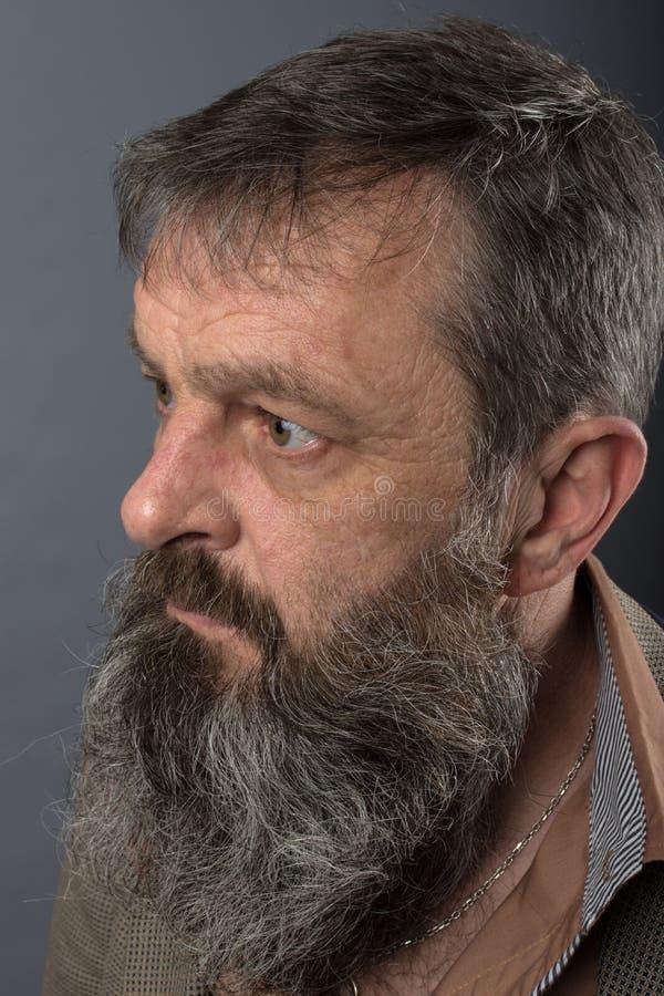 Foto van een boze knorrige oude mens die zeer ontstemd kijken Mannelijke mens met lange baard op zijn gezicht Sluit omhoog gezich stock foto's