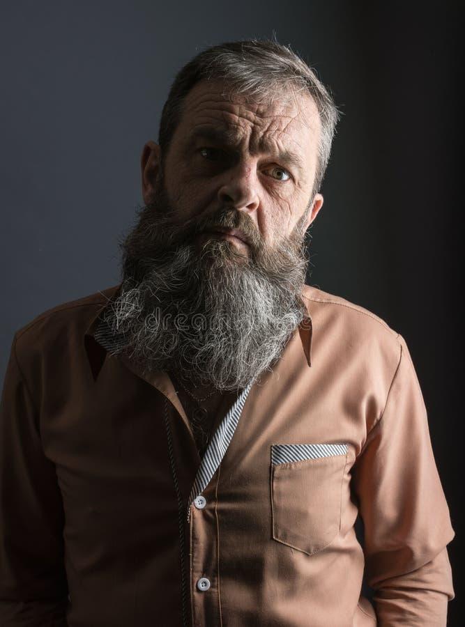 Foto van een boze knorrige oude mens die zeer ontstemd kijken Mannelijke mens met lange baard op zijn gezicht Sluit omhoog gezich royalty-vrije stock foto