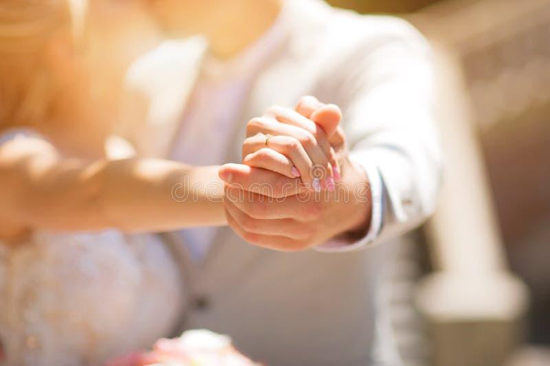 Foto van een huwelijkspaar in de zomer Bruid en bruidegom het koesteren, handen, ringen, het close-up van het huwelijksboeket en  royalty-vrije stock afbeeldingen