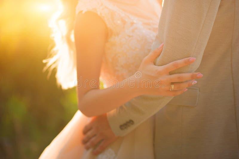Foto van een huwelijkspaar in de zomer Bruid en bruidegom het koesteren, handen, ringen, het close-up van het huwelijksboeket en  royalty-vrije stock afbeelding