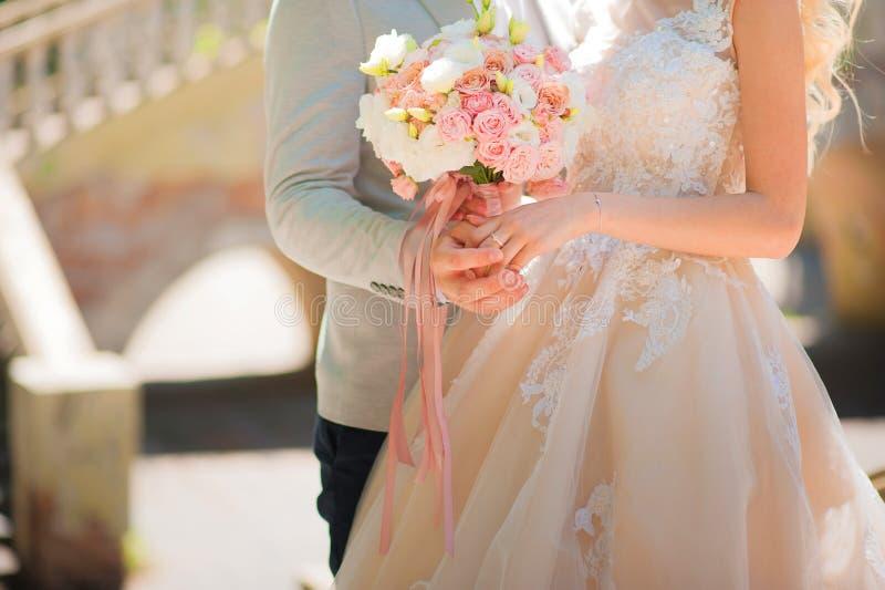 Foto van een huwelijkspaar in de zomer Bruid en bruidegom het koesteren, handen, ringen, het close-up van het huwelijksboeket en  stock afbeelding