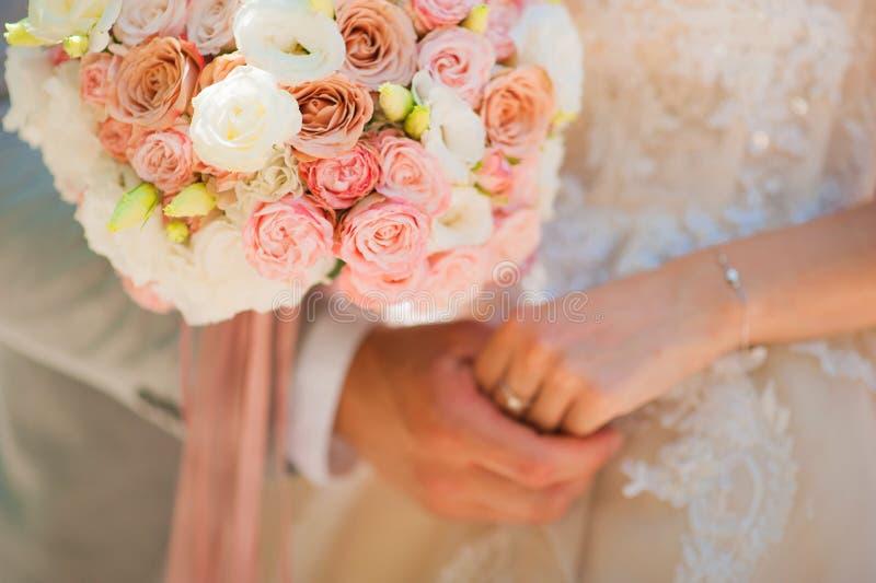 Foto van een huwelijkspaar in de zomer Bruid en bruidegom het koesteren, handen, ringen, het close-up van het huwelijksboeket en  stock foto